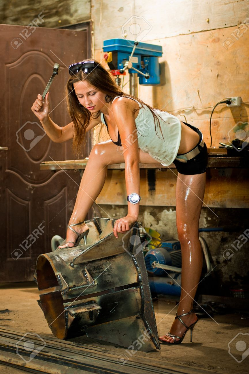 Woman in dirty t-shirt working with tools in garage Stock Photo - 8629415