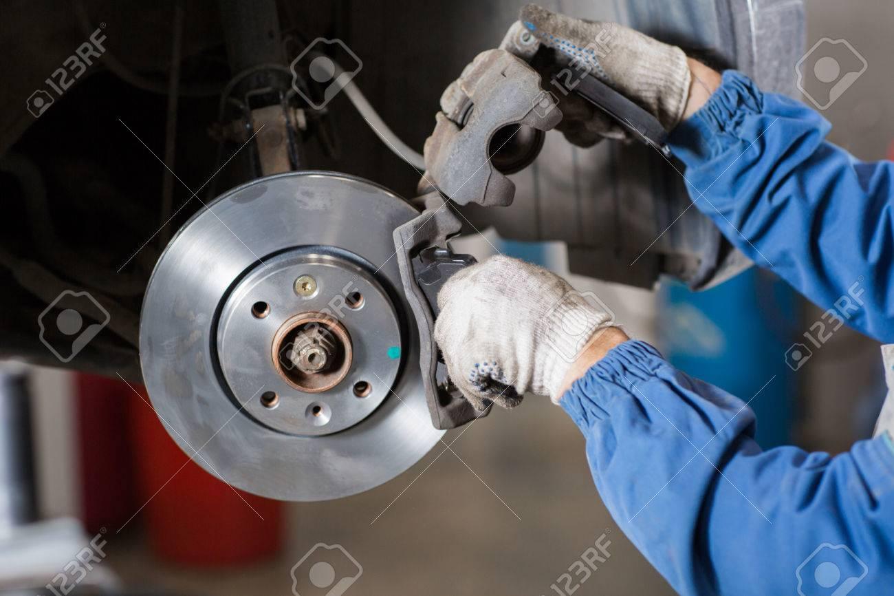 Brand new brake disc on car in a garage. Auto mechanic repairing a car. - 62890250