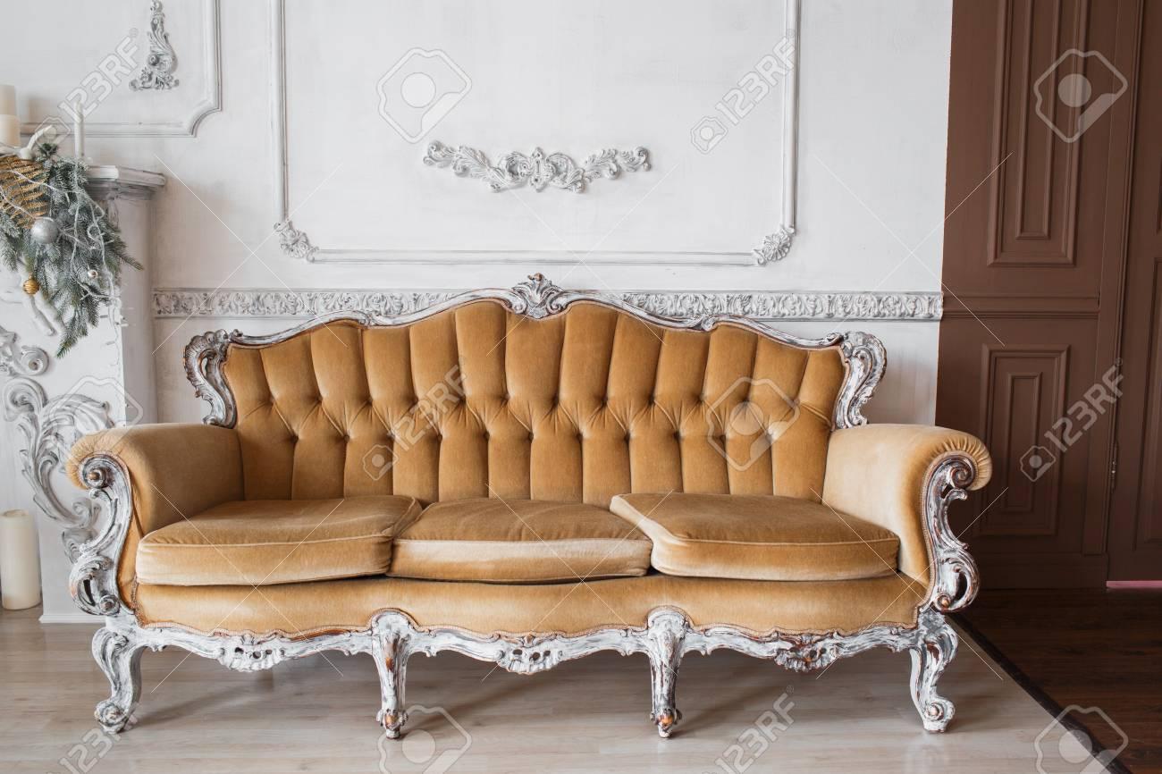 Standard Bild   Wohnzimmer Mit Antiken Stilvollen Beige Sofa Auf  Luxus Weißen Wand Design Basrelief Stuck Formteile Rokoko Elemente. Schwarz  Weiß Foto