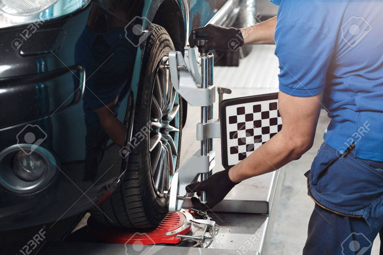 Grid sensor sets mechanic on auto. Car on stand with sensors wheels for alignment camber check in workshop of Service station - 66984503