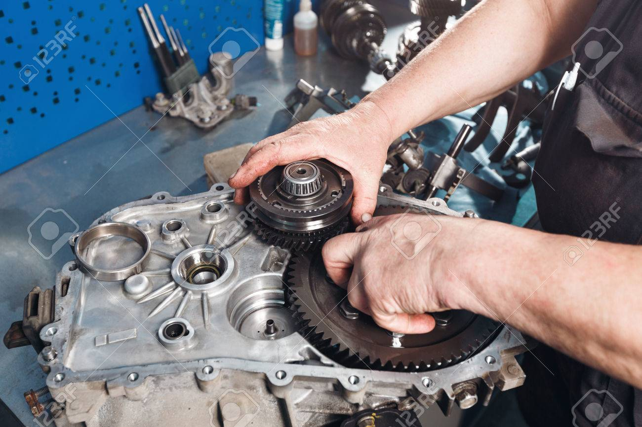 Cross-section of a car gearbox. mechanics work in the garage. hand car mechanic in working clothes. - 67027593
