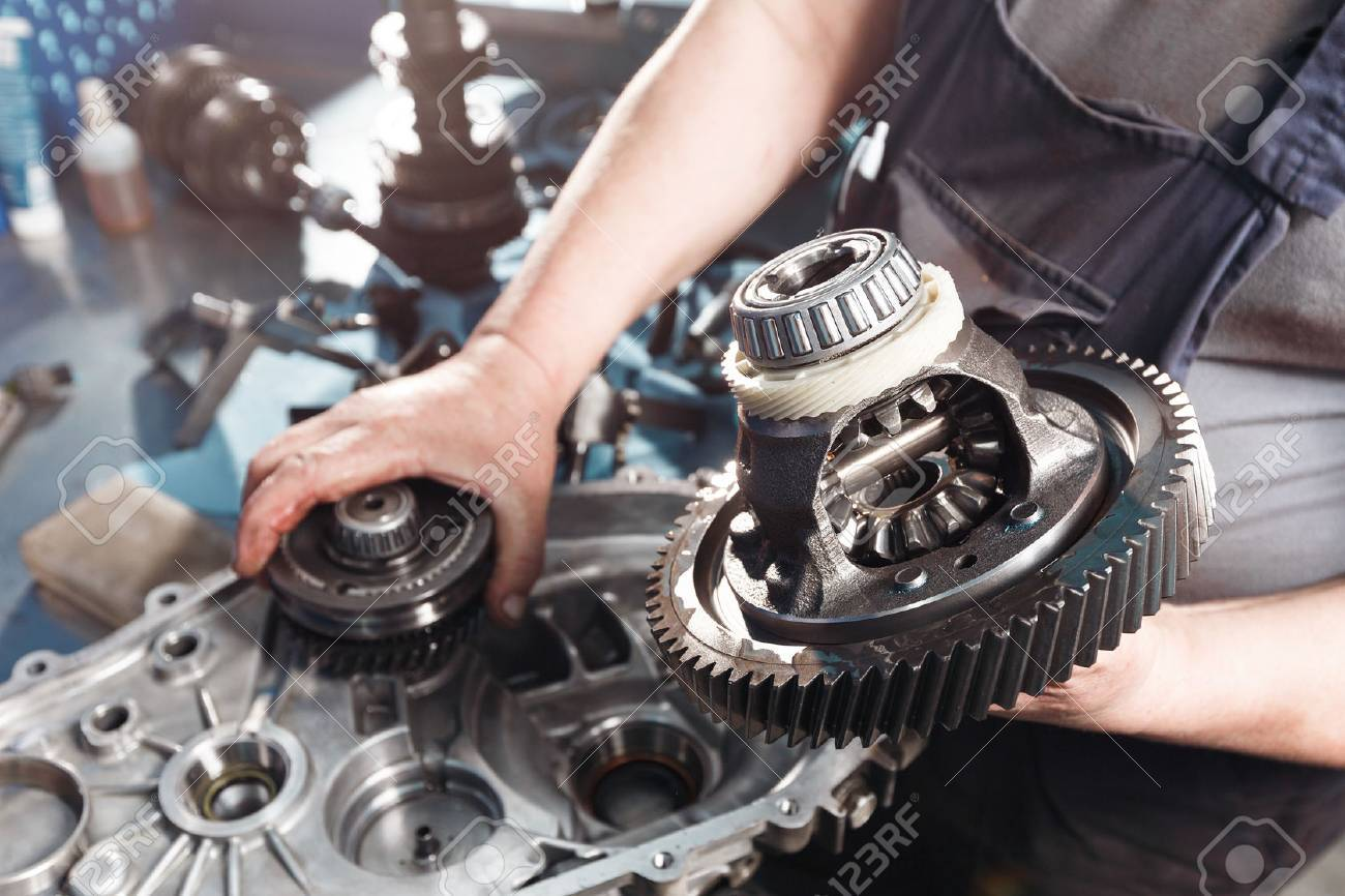Cross-section of a car gearbox. mechanics work in the garage. hand car mechanic in working clothes. - 67078342