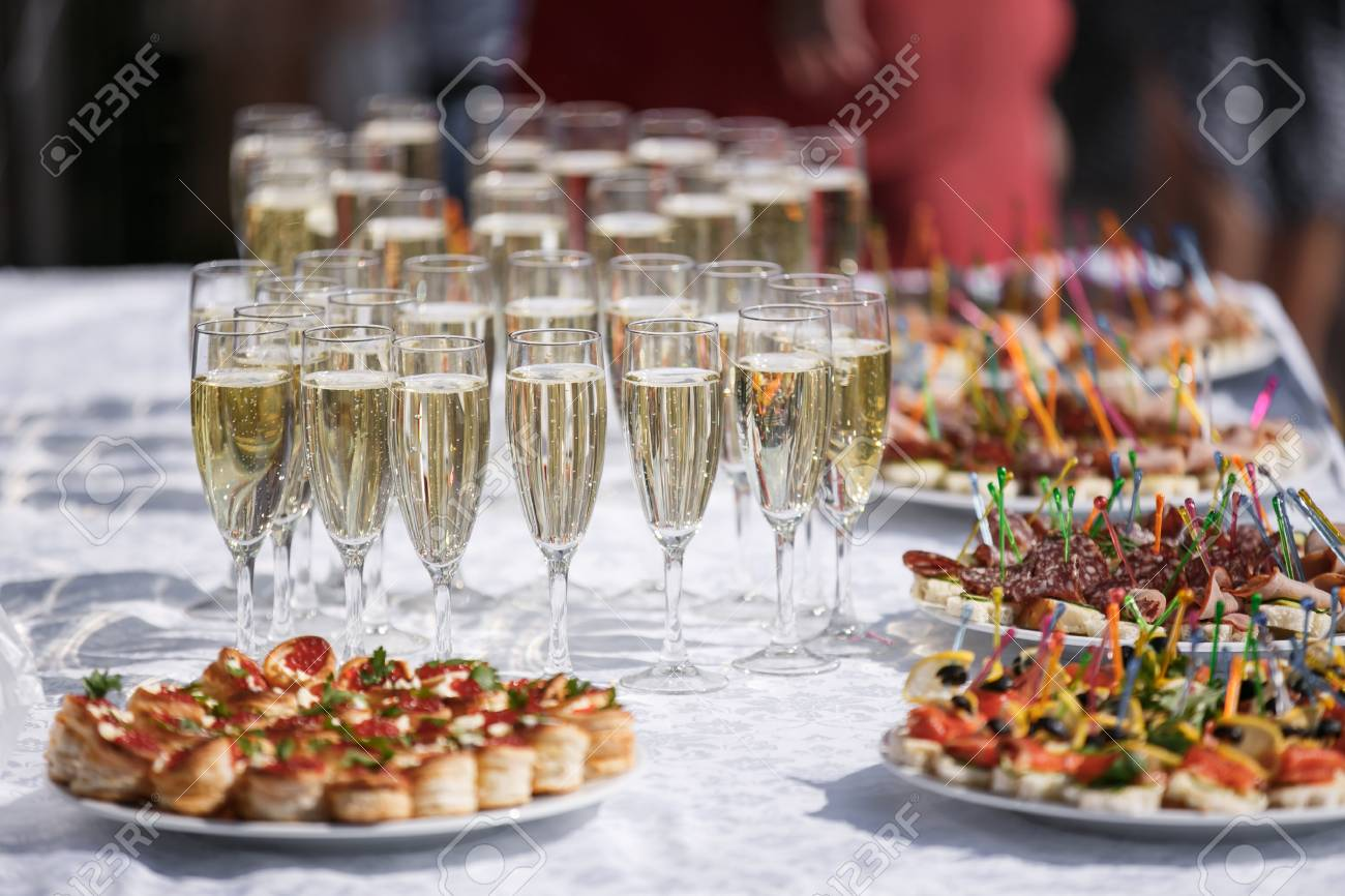 glasses with champagne. catering banquet table. a lot of snacks and canapes - 74679085
