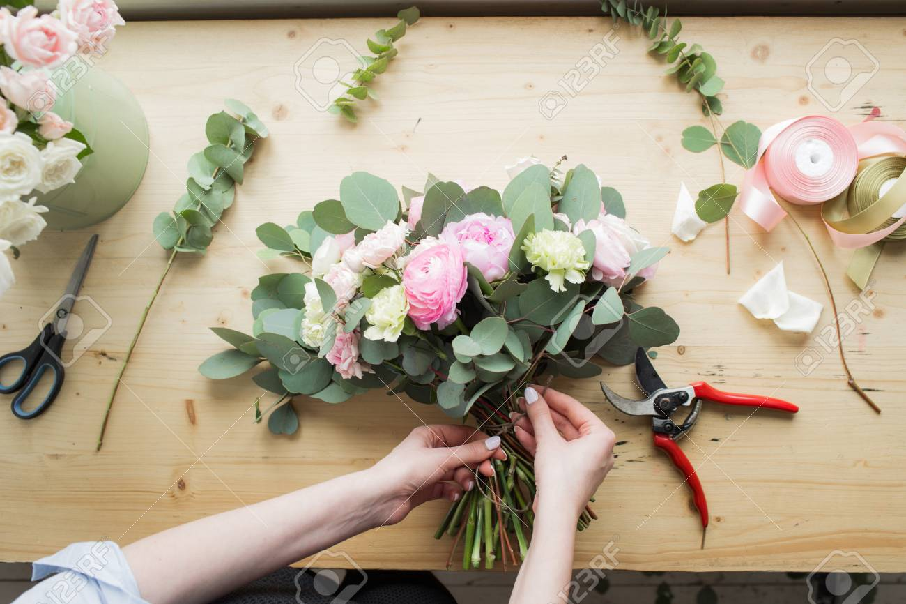 Florist at work: pretty young woman making fashion modern bouquet of different flowers - 75968133