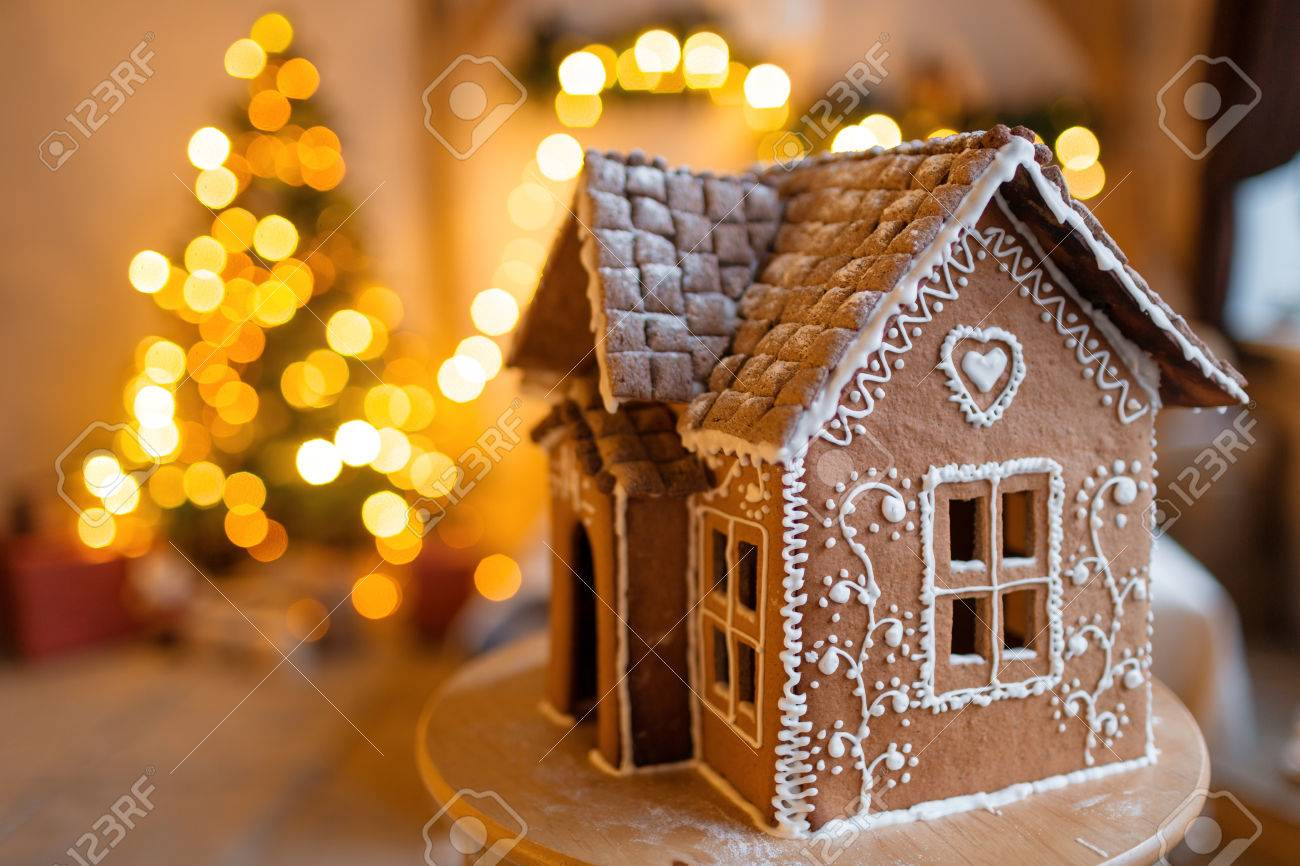 gingerbread house over defocused lights of Chrismtas decorated fir tree - 88360405