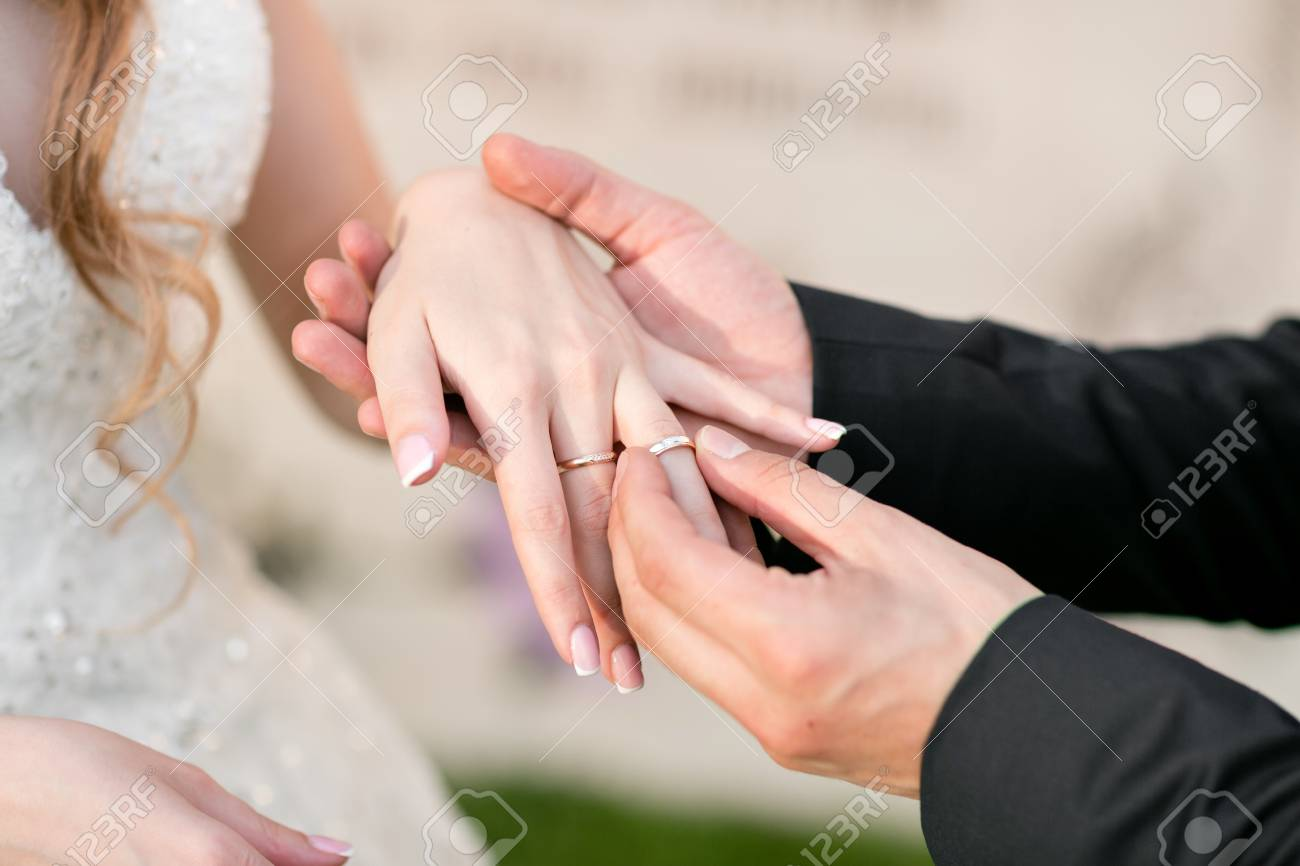 Wedding Rings And Hands Of Bride And Groom. Young Wedding Couple ...