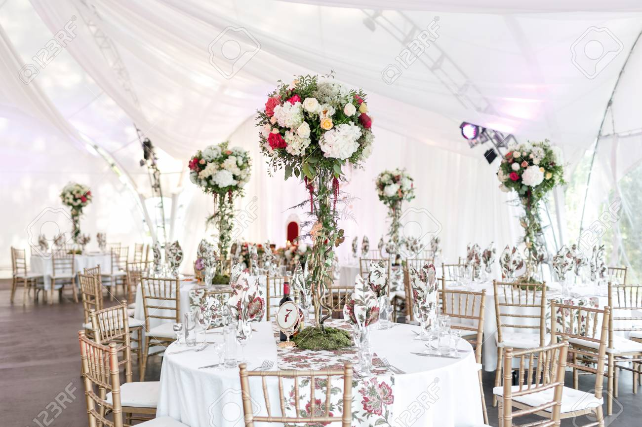 Interior of a wedding tent decoration ready for guests. Served round banquet table outdoor in marquee decorated flowers and silk. Catering concept. - 93064607