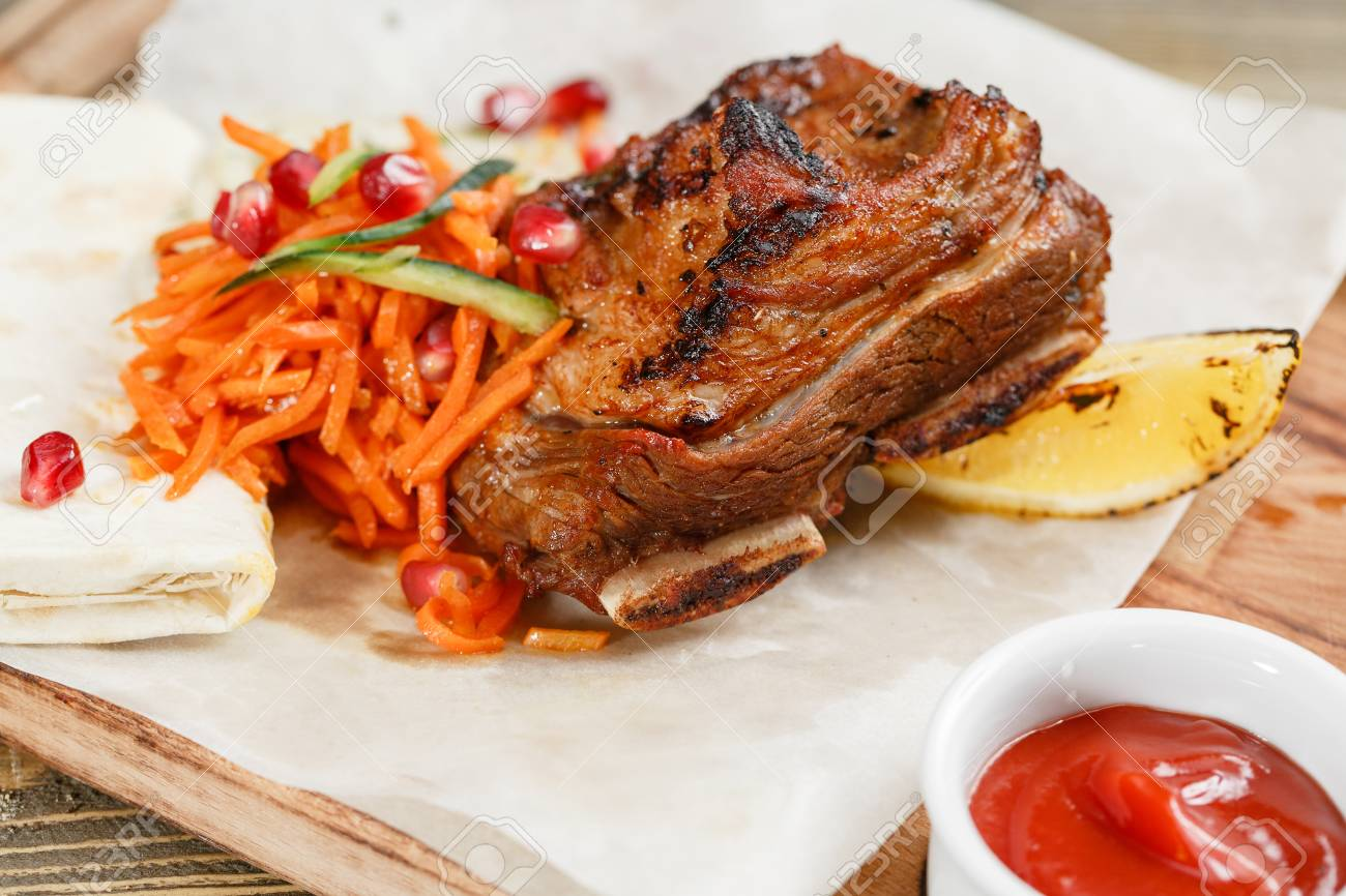 Grilled Beef Ribs Serving On A Wooden Board On A Rustic Table
