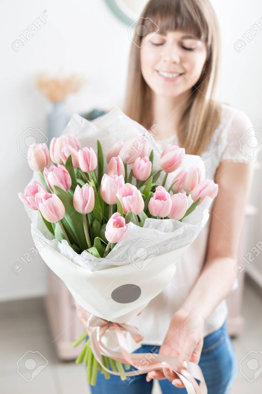 Sunny spring morning young happy woman holding a beautiful bunch young happy woman holding a beautiful bunch of pink tulips in her hands present for a smiles girl flowers bouquet izmirmasajfo