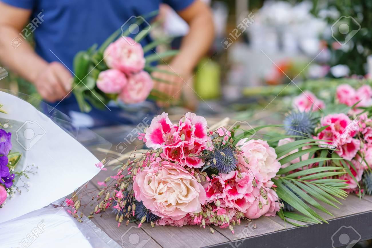 Male Florist Creating Beautiful Bouquet In Flower Shop Outdoor