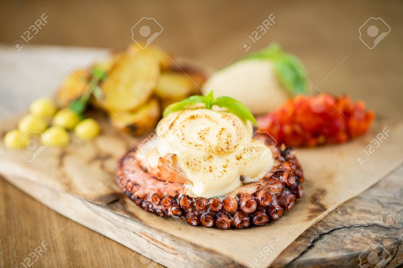 Roasted octopus BBQ with Baked potato. Wooden plate. Restaurant menu - 130485029