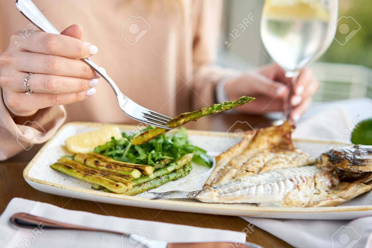 Lunch in a restaurant, a woman eats roasted dorado fish with grilled asparagus. Dish decorated with a slice of lemon. Restaurant menu - 133566688
