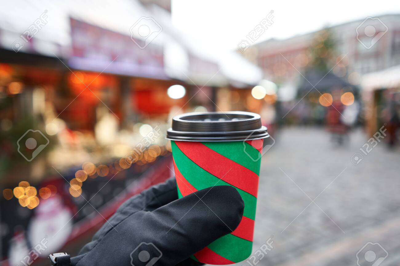 Hand holding a cup of mulled wine with blurred background of winter wonderland, a Christmas Market in European small city. - 135518611