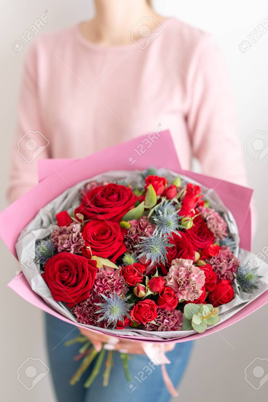 Mixed bouquet of red tones. Beautiful bunch of fresh flowers in womans hands. The work of the florist at a flower shop. Fresh cut flower - 139976934