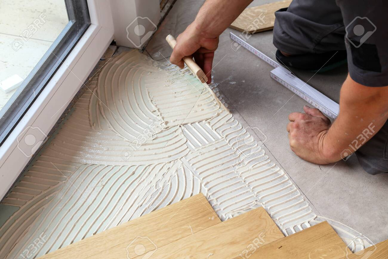 Worker laying parquet flooring. Worker installing wooden laminate flooring - 128392638