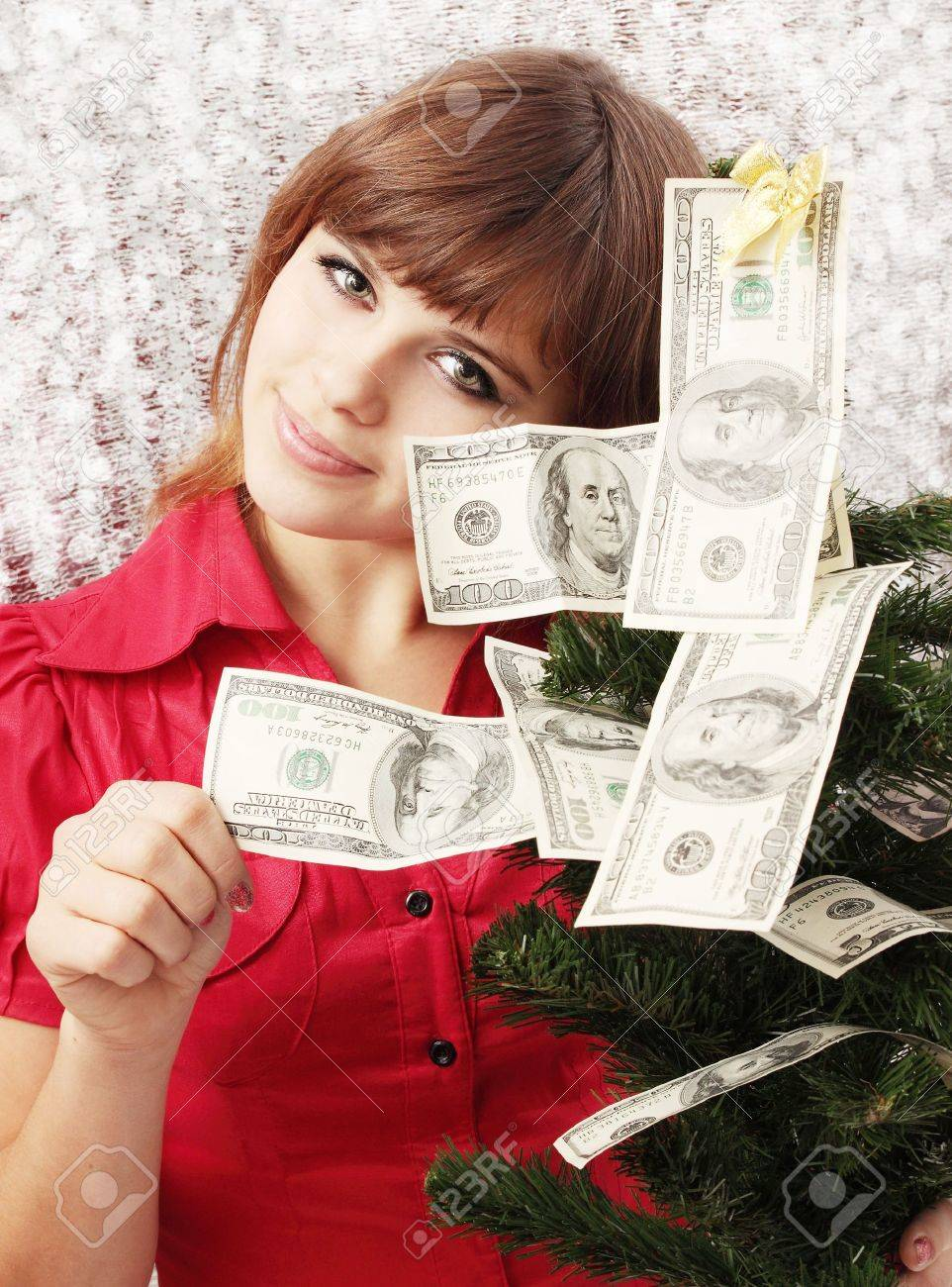 Girl holds Christmas tree decorated with money Stock Photo - 8216809