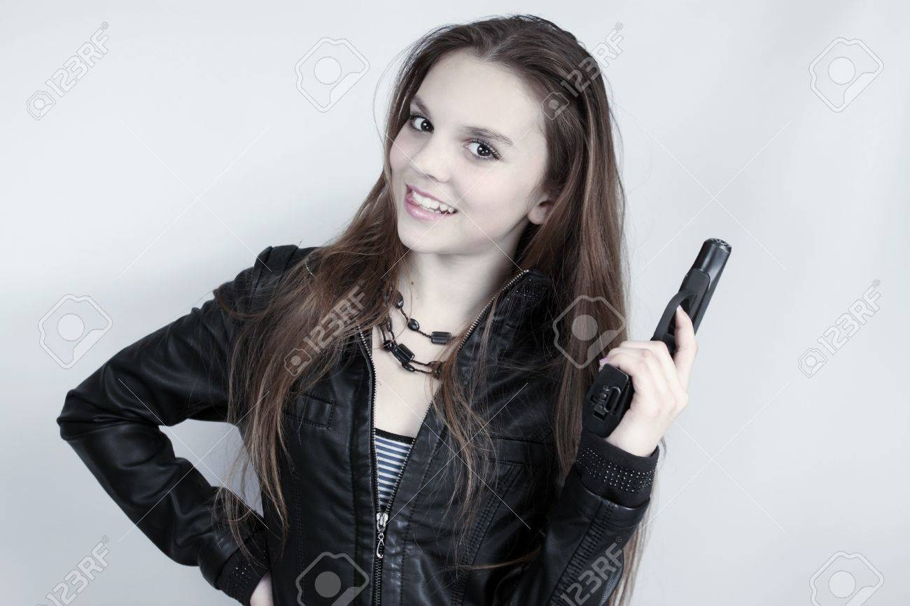 Young beautiful girl holds in the hand the pistol Stock Photo - 12939912