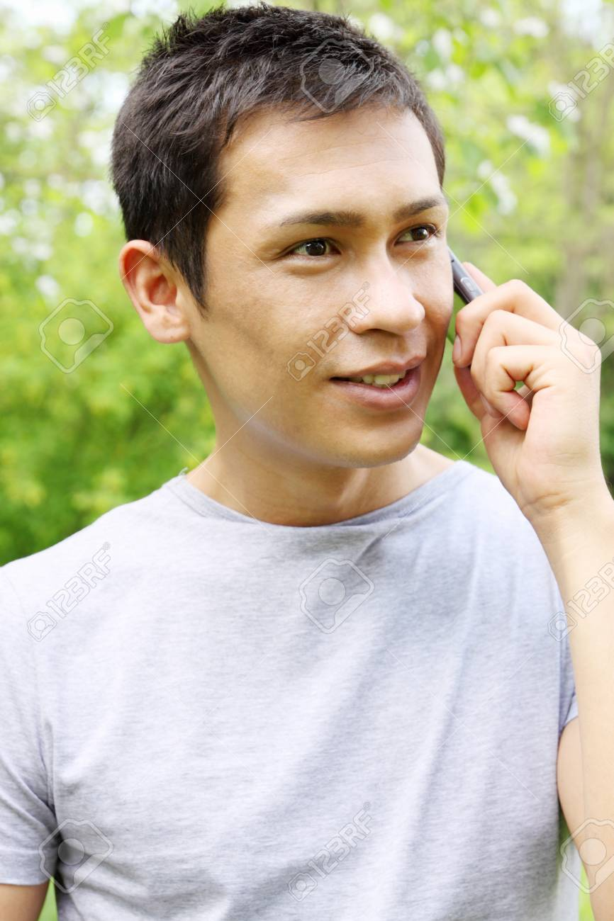 Handsome young man speaks on a mobile phone Stock Photo - 14903784