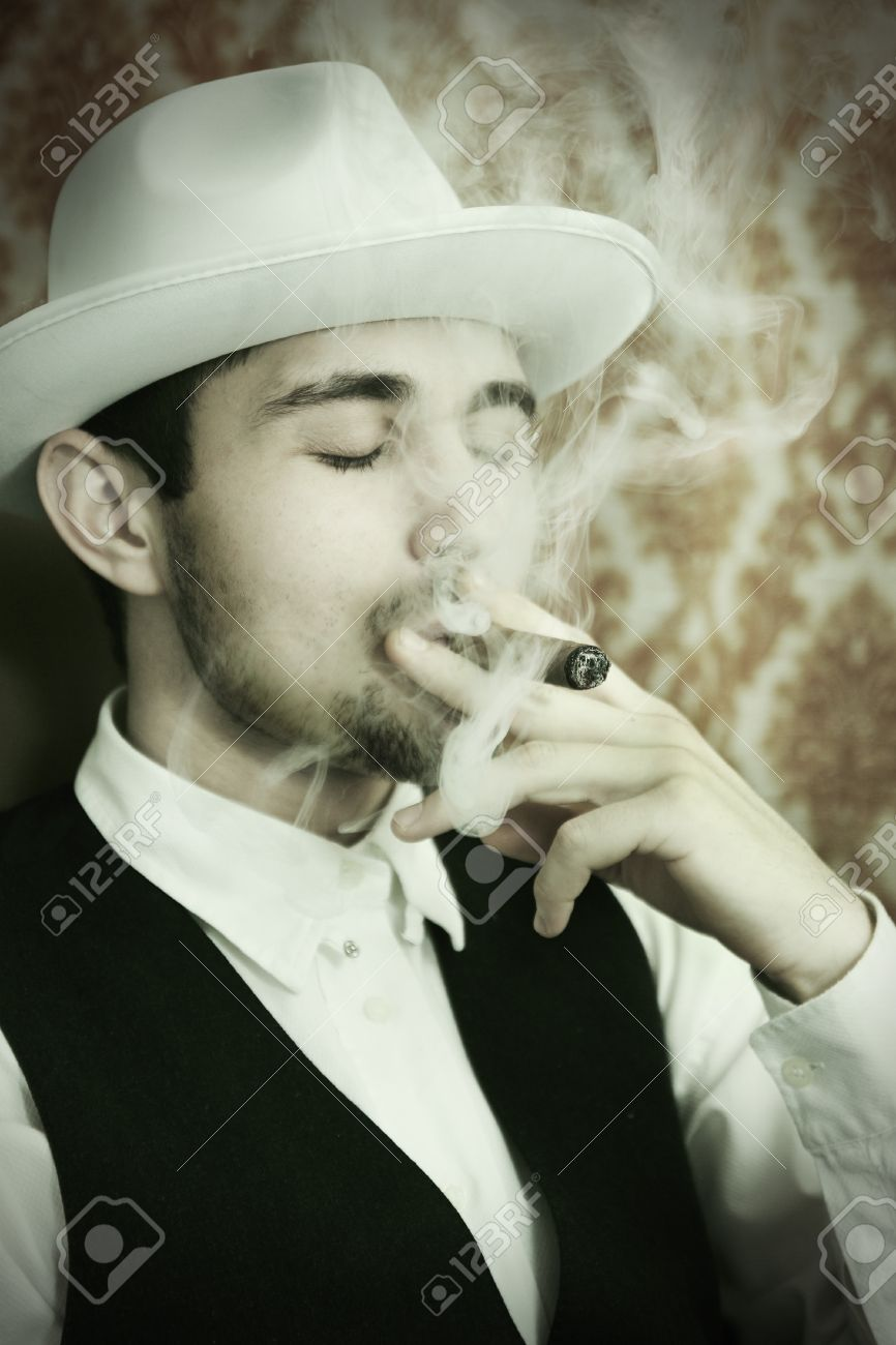 A young man in a hat with a cigar Stock Photo - 16949103