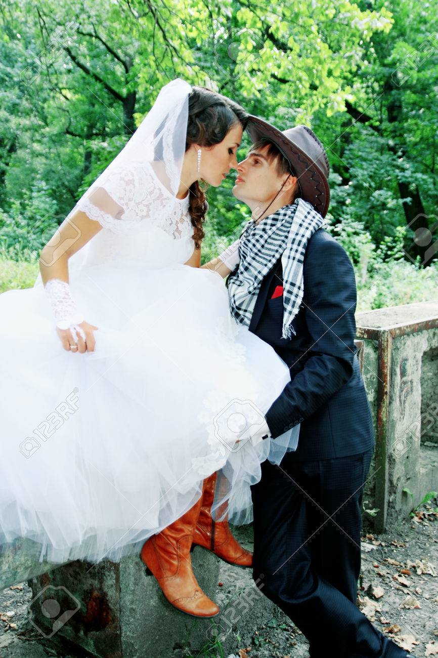 5bbd3cf225f Bride kissing groom in a cowboy hat Stock Photo - 32253860