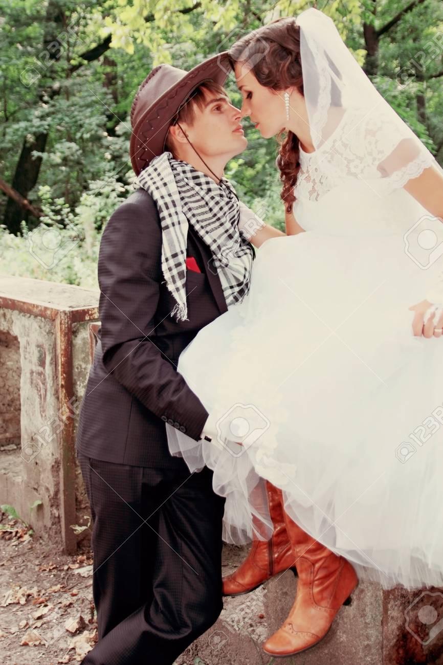 830621696af Bride kissing groom in a cowboy hat Stock Photo - 32254014