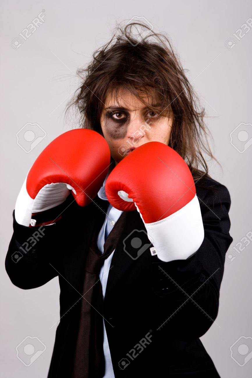 businesswoman wearing boxing gloves with bruised eye. grey background. Stock Photo - 4091819