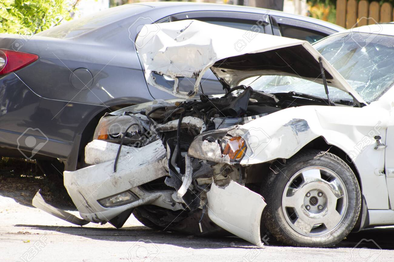 A road accident, a car that crashed, a white car on the road, cracks in the glass and a damaged bumper. - 153976013