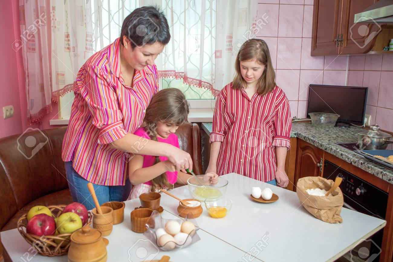 Mom teaching her two children cooking on the kitchen  Parent