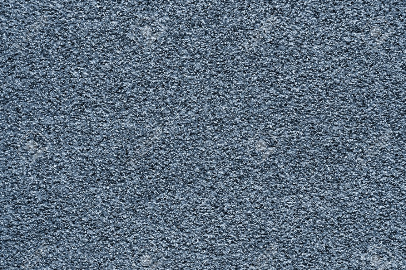 granular texture of a dark gray abrasive material for an abstract background stock photo