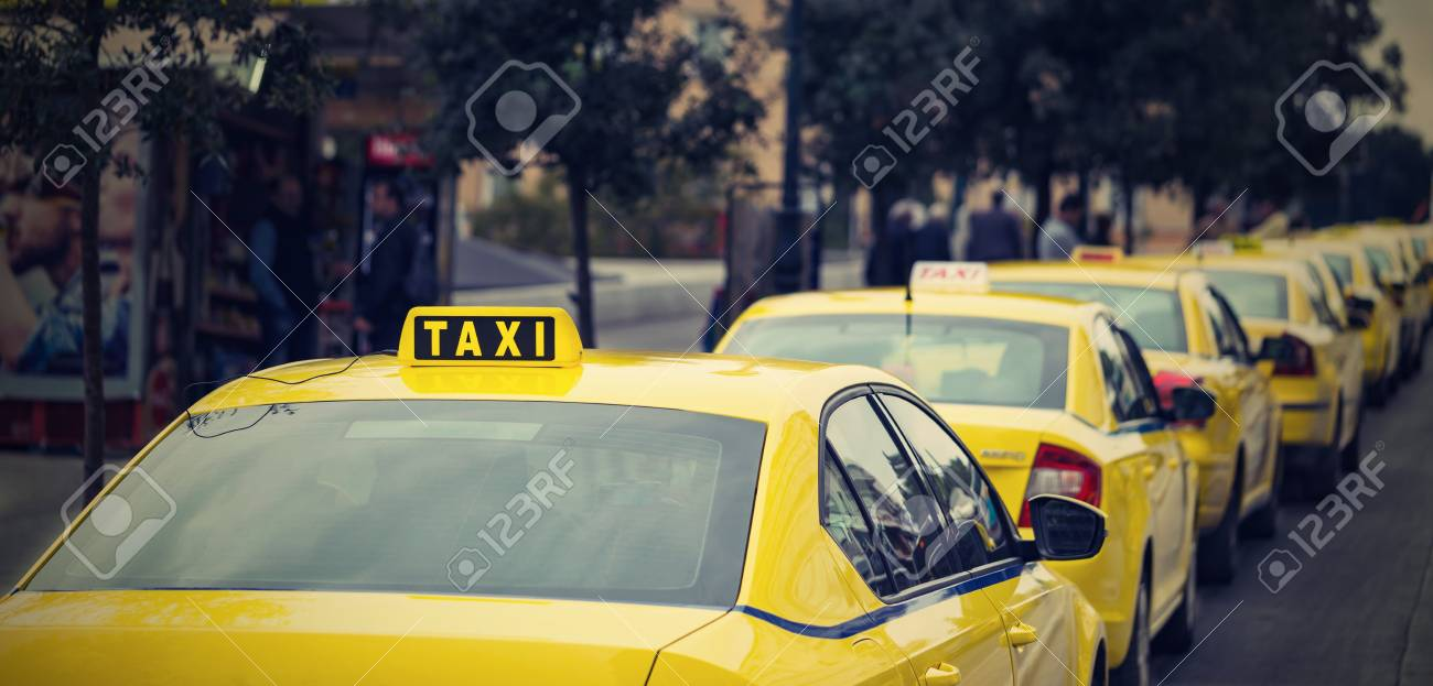 Yellow Cars Of The Taxi On The City Street And On The Color Photo ...