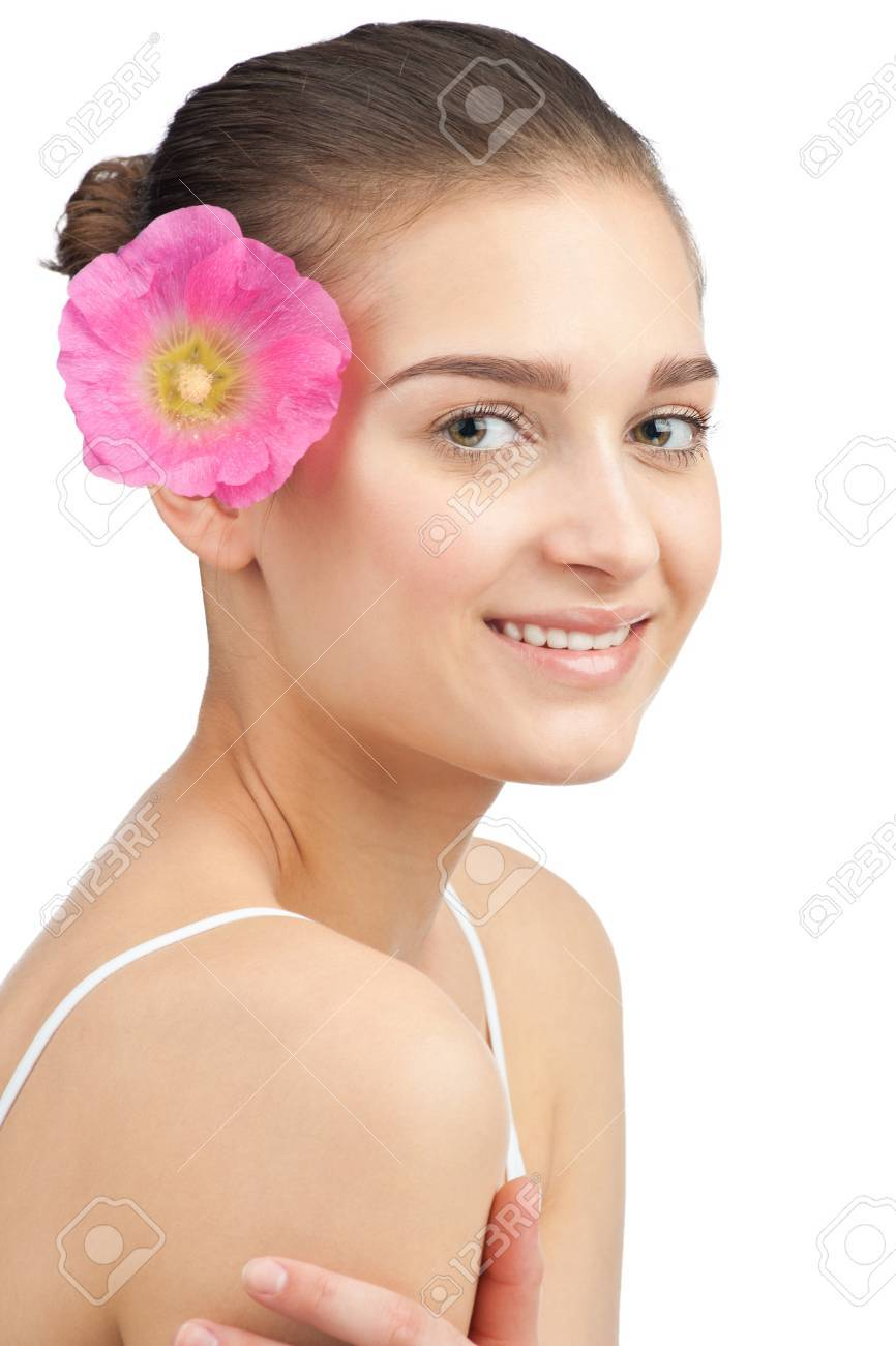 Portrait of young beautiful spa woman with pink flower in her hair. Isolated on white background Stock Photo - 10841401