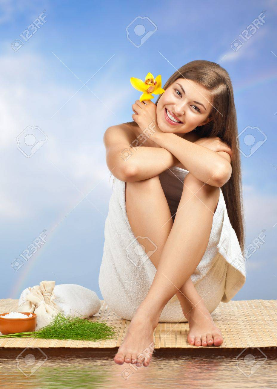 Portrait of young beautiful spa woman sitting on bamboo mat against blue sky and water Stock Photo - 10845742