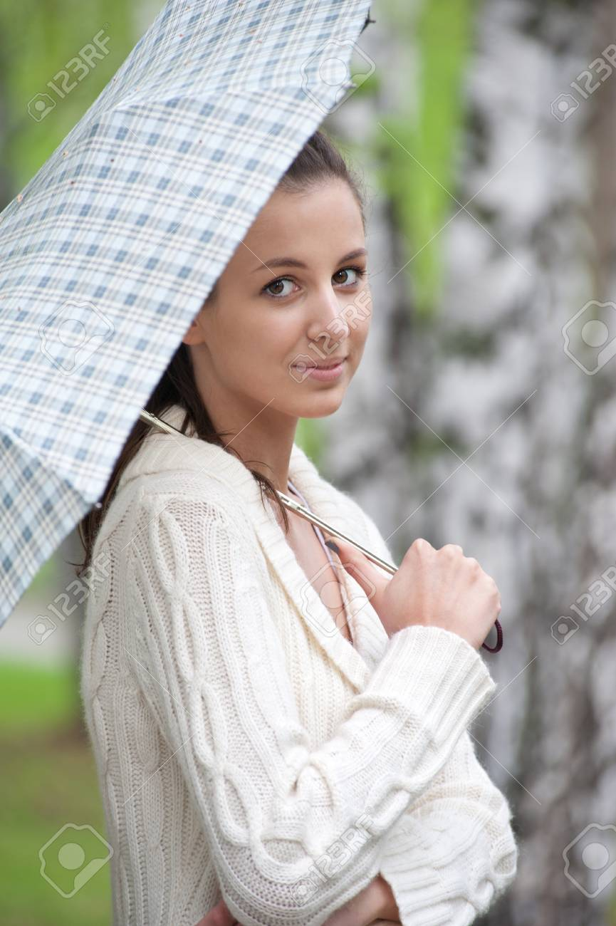 Young beautiful woman with umbrella walking in park Stock Photo - 10855470