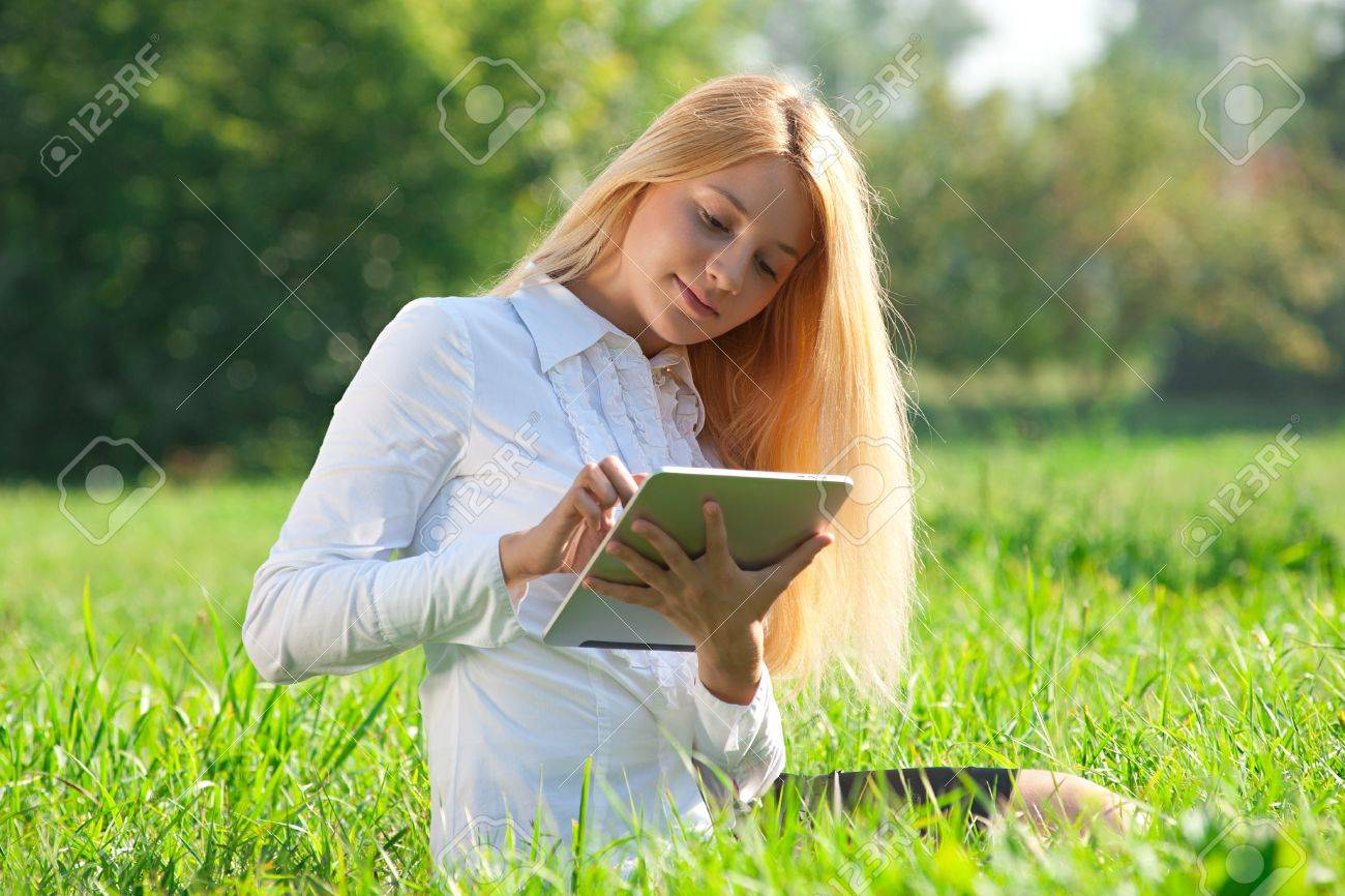 Young  business woman sitting on grass and using electronic tablet outdoors Stock Photo - 10947966