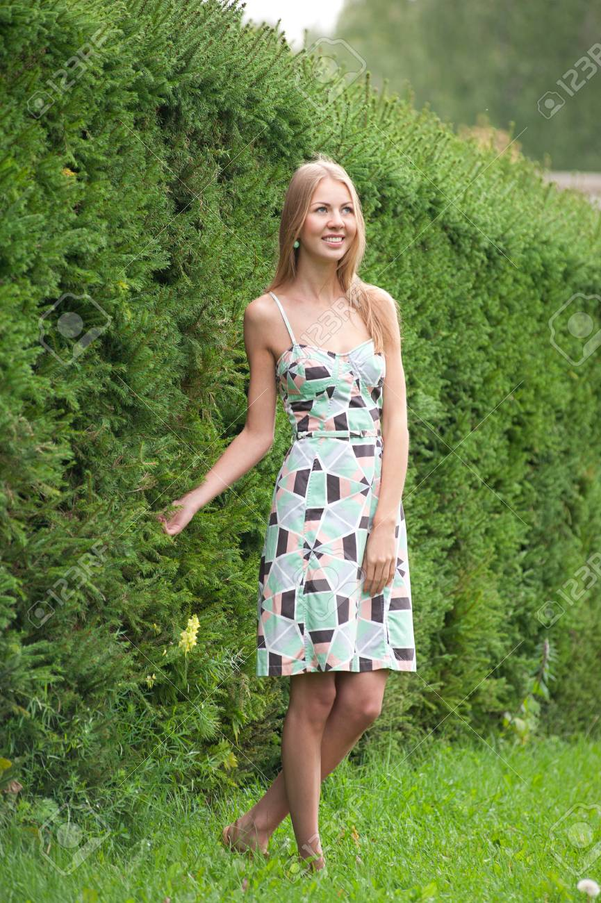 2bdb089128 Stock Photo - Young woman wearing summer dress standing outside in park and  smiling