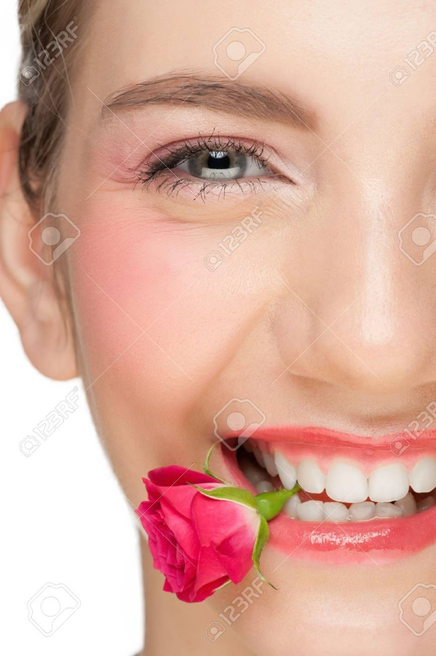 Close-up portrait of young beautiful woman with pink make-up holding pink rose bud in her mouth Stock Photo - 11955244