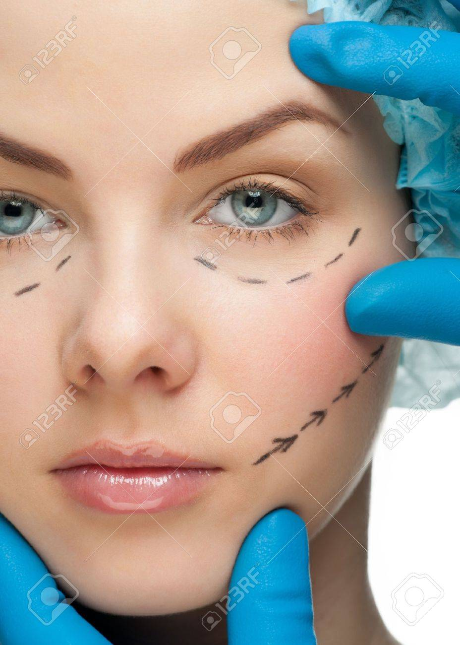 Beautiful young woman with perforation lines on her face before plastic surgery operation. Beautician touching woman face. Stock Photo - 11955166