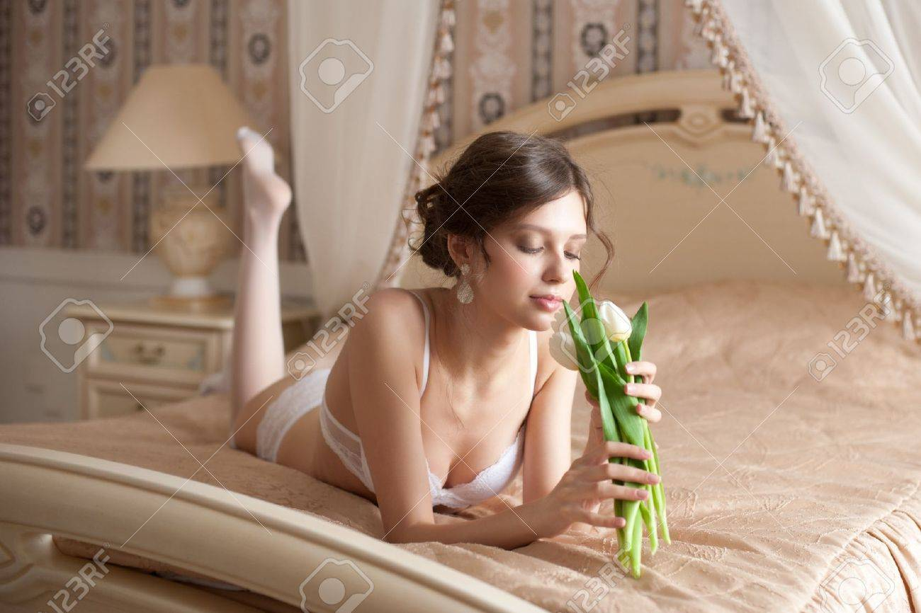 Beautiful bride in white lingerie with bouquet of white tulips lying on the bed in her bedroom Stock Photo - 13322568