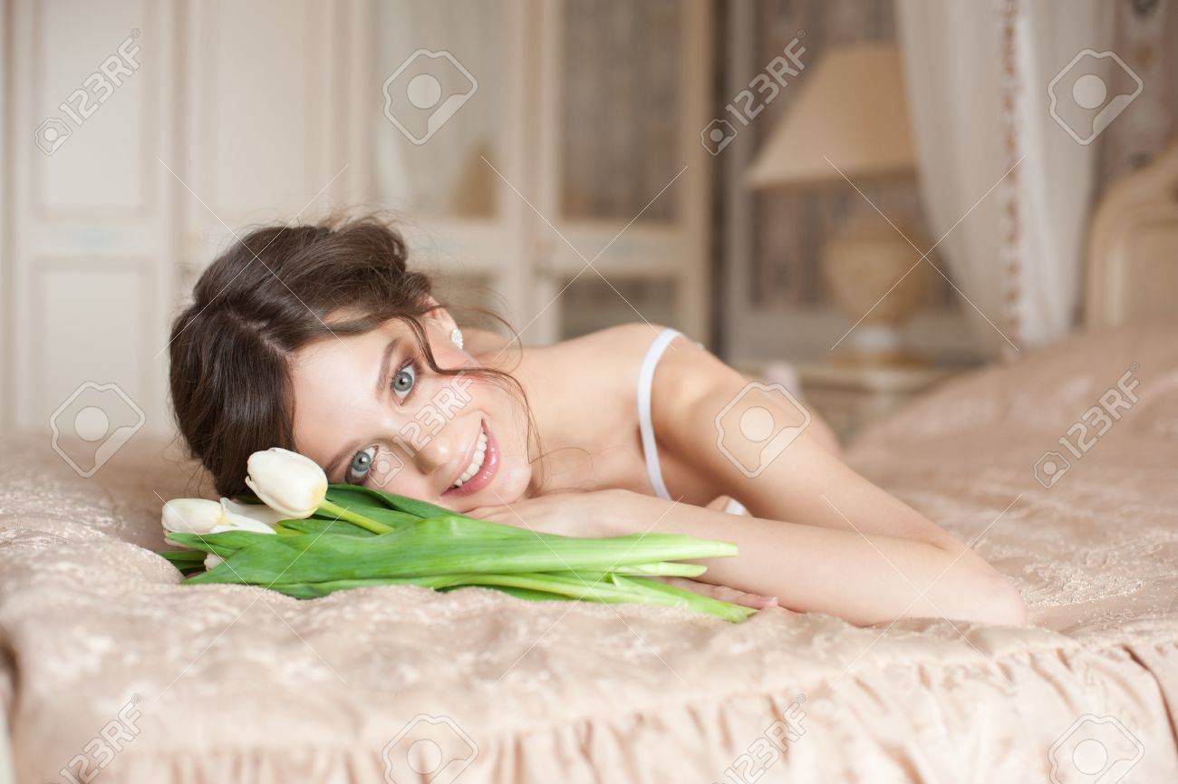 Beautiful bride in white lingerie with bouquet of white tulips lying on the bed in her bedroom Stock Photo - 13322755