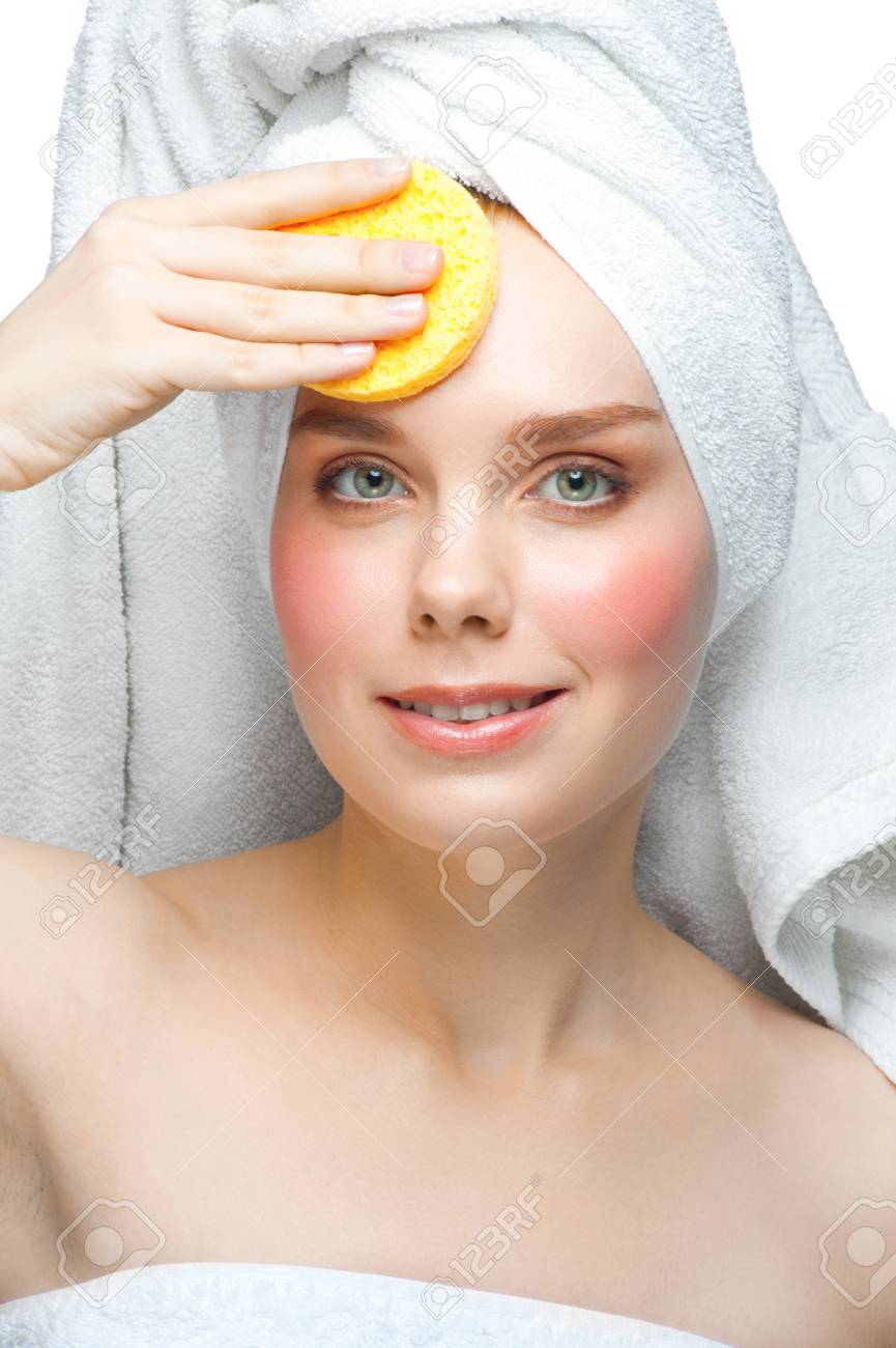 Portrait of young beautiful woman in white towel with bath sponge cleaning her face. Isolated on white background Stock Photo - 13645102