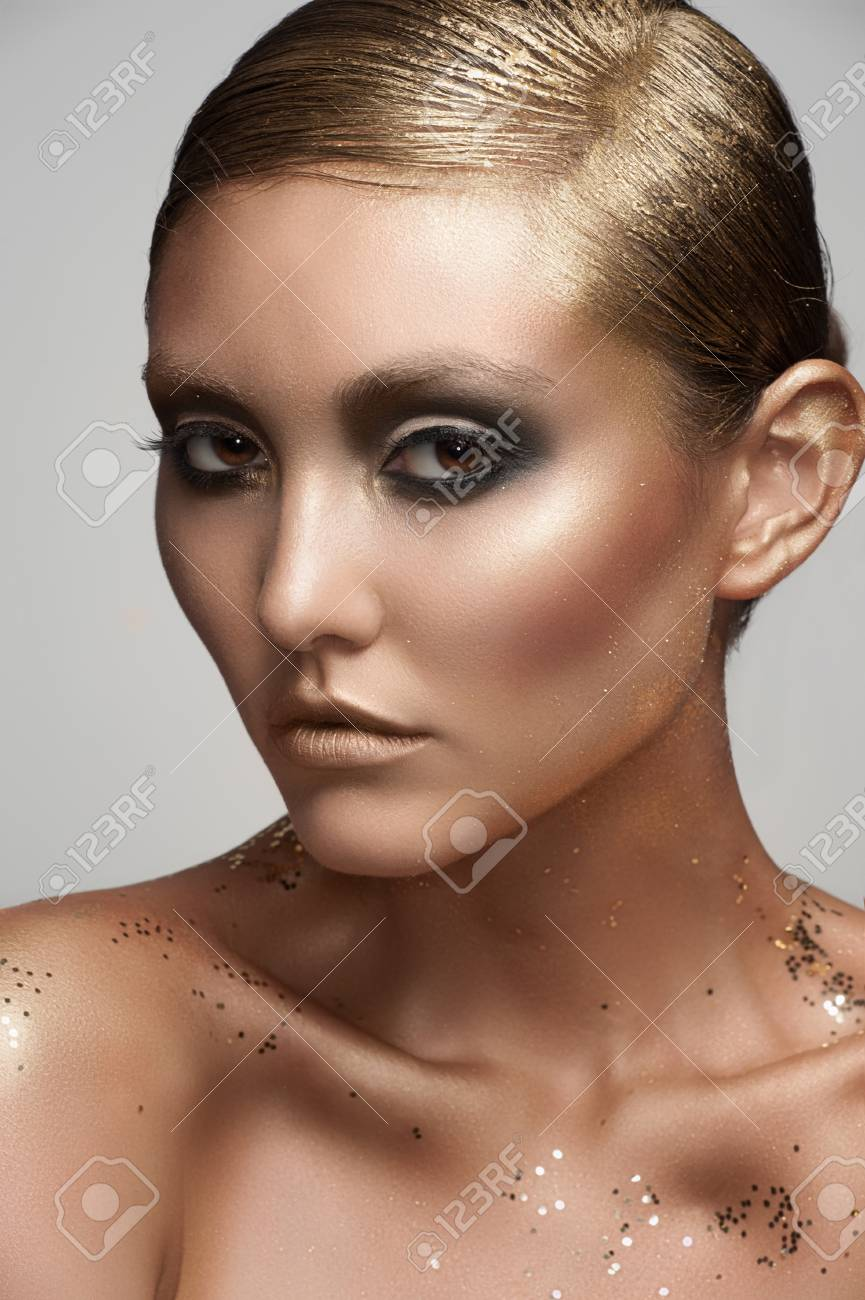 Portrait of attractive young woman with creative golden makeup Stock Photo - 17255271