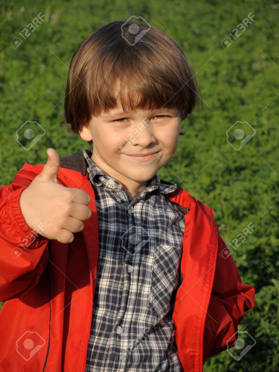 Portrait of a smiling young boy gesturing thumbs on the nature. Happiness, fashionable concept. Lifestyle. - 43075985