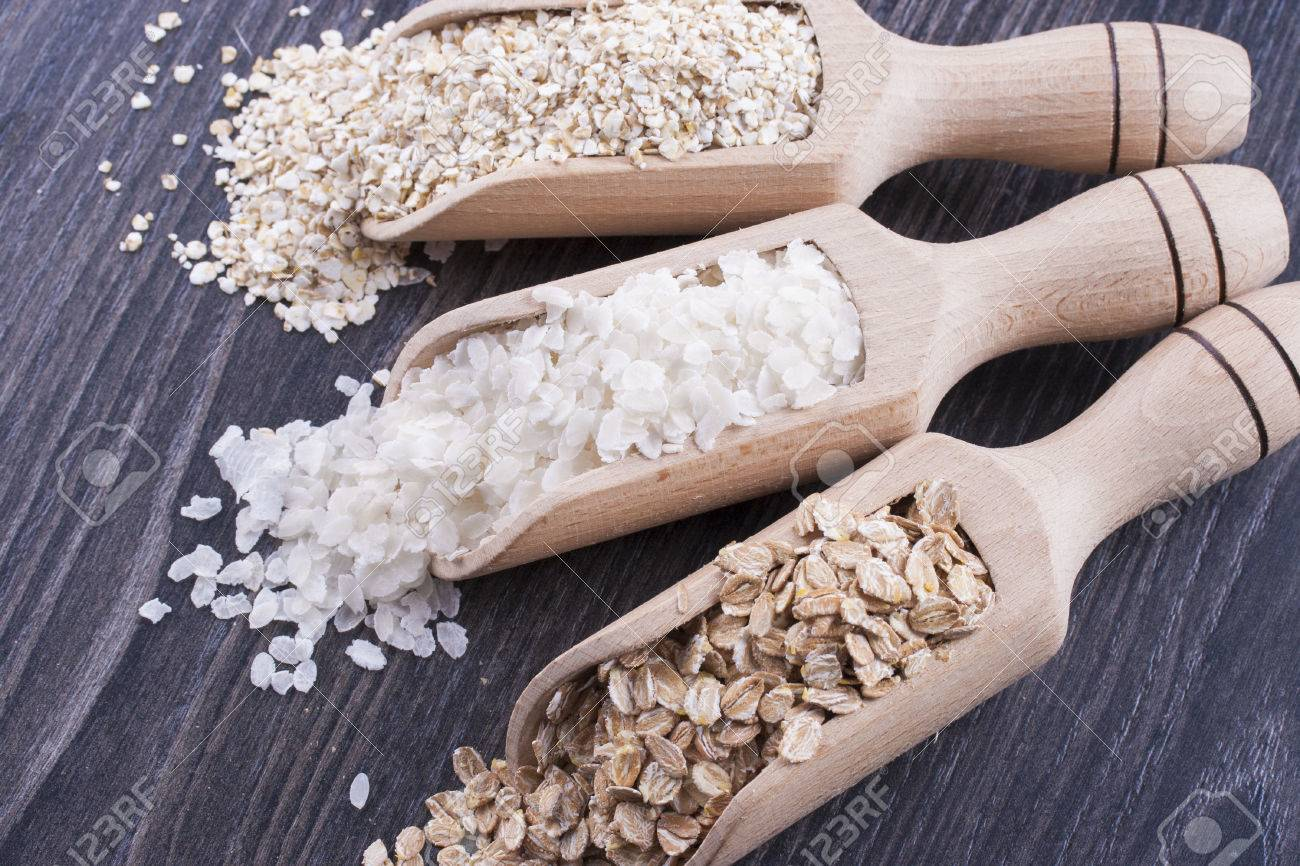 Close up photo of a breakfast cereal in a wooden scoop - light brown barley flakes, white rice flakes and dark brown secale flakes placed on a dark wooden background. Stock Photo - 22214076