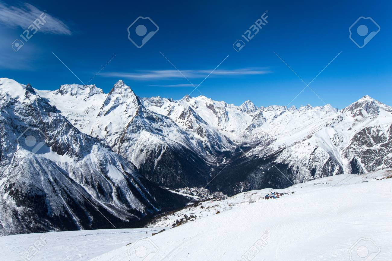 Snow Capped Alpine Mountain Ranges Extending Into The Distance And The Village Below Panorama