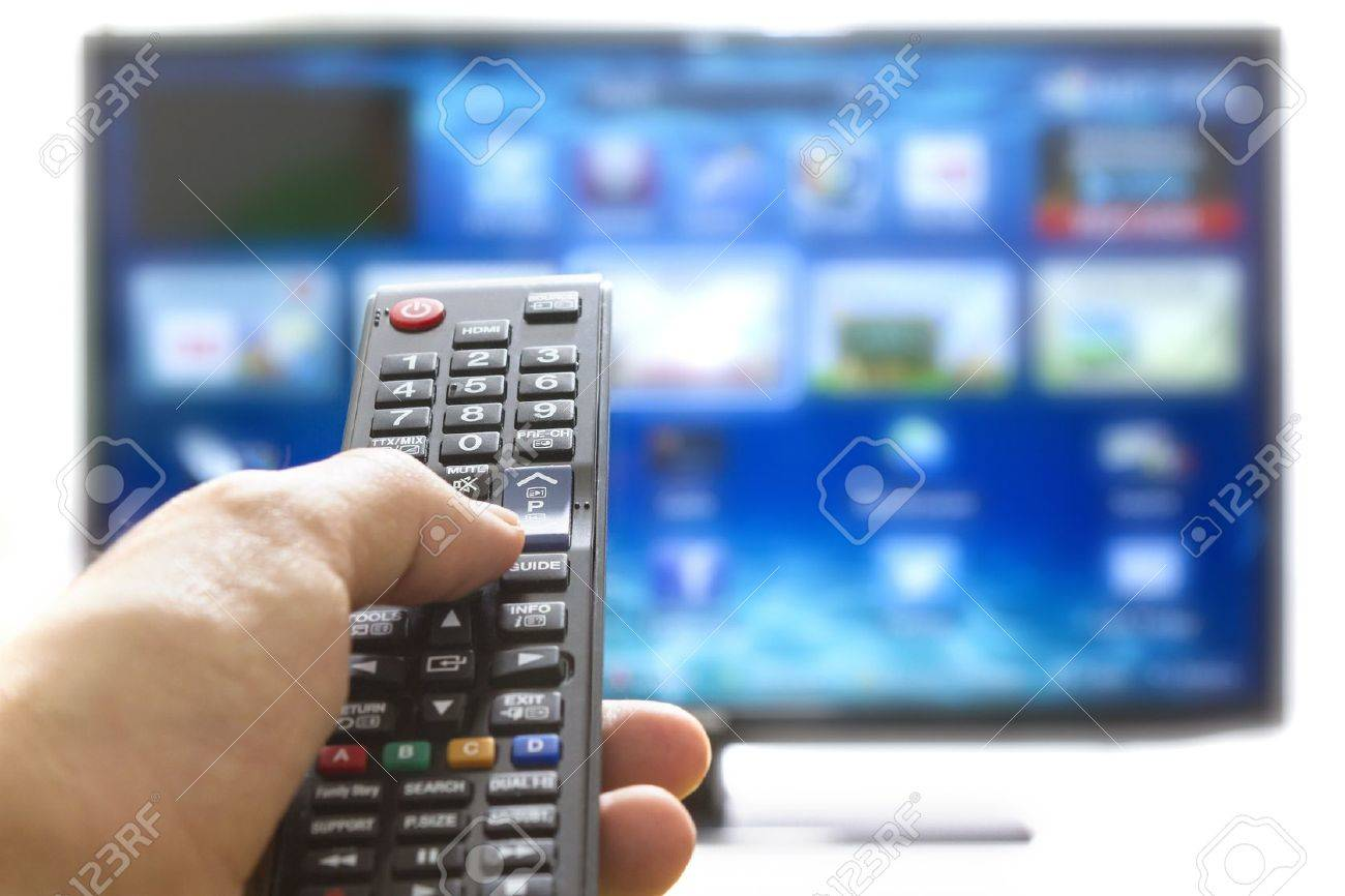 Television remote control changes channels thumb on the blue TV screen - 17696699