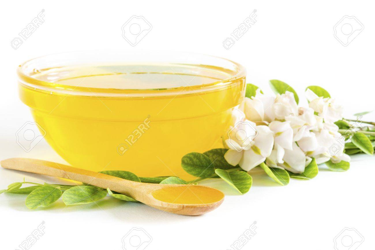Honey in glass bowl and acacia on white background - 19793115
