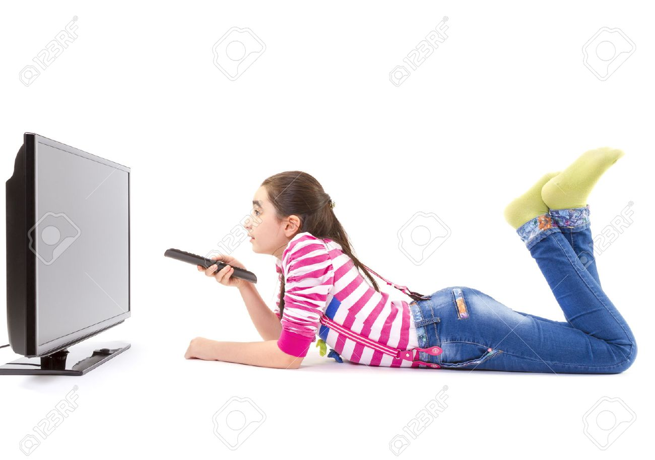 happy little girl laying down and watching tv stock photo picture