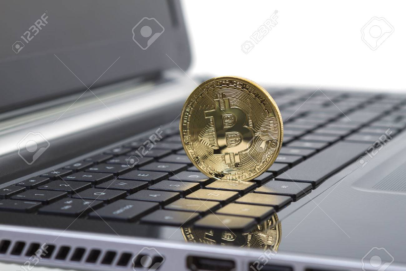 Studio shot of golden Bitcoin virtual currency on laptop. Close-up of front side. - 29292834