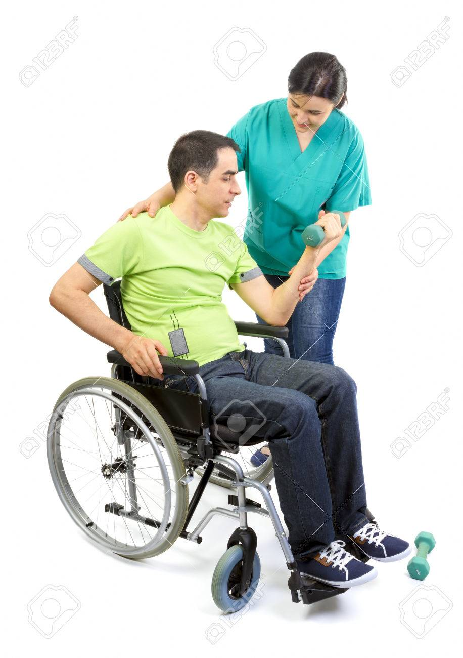 Physical therapist works with patient in lifting hands weights Young adult in wheelchair - 30165563