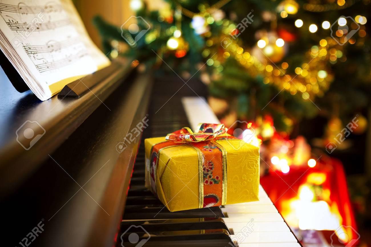 Christmas gift on piano. Christmas decoration with gift on piano - 32919998